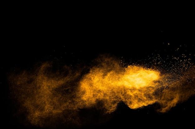 Bevries de beweging van spatten van geeloranje stofdeeltjes