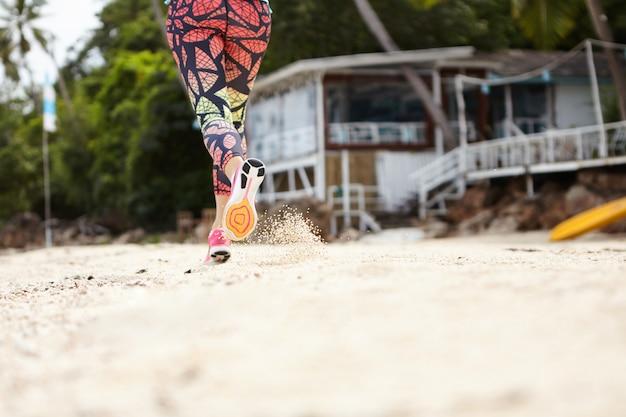 Bevriezen actie shot van vrouw jogger in sportkleding draait op zandstrand op zonnige dag.