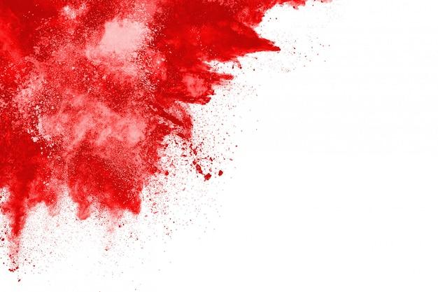 Bevriezen beweging van exploderend rood poeder, geïsoleerd op een witte achtergrond.