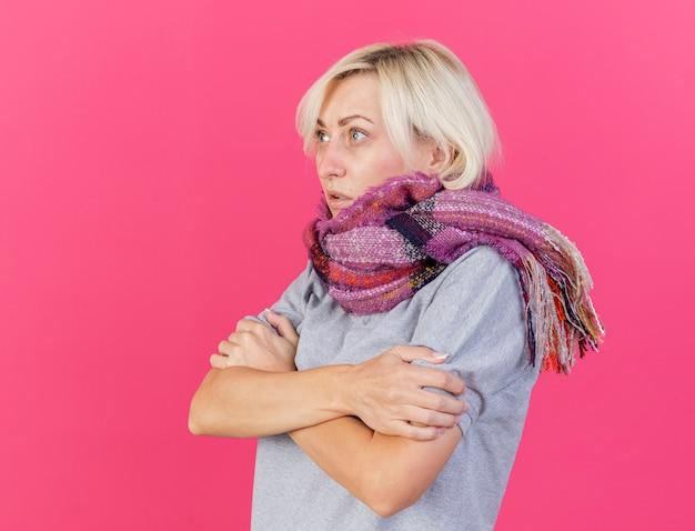 Bevriezende jonge blonde zieke slavische vrouw die sjaal draagt houdt wapens die kant op roze bekijken