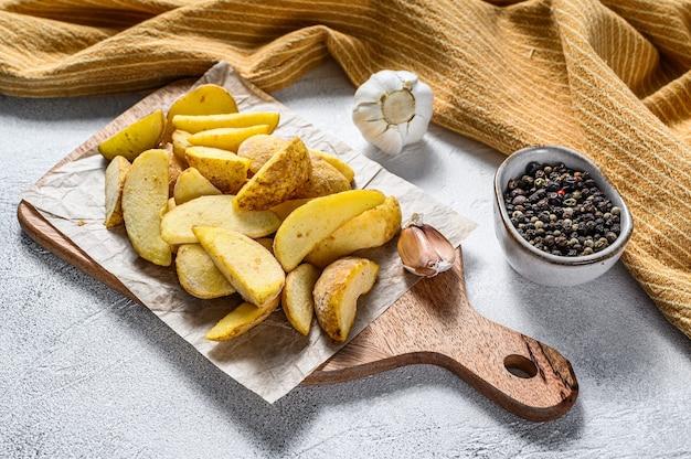 Bevroren aardappelpartjes op een snijplank. recept voor frietjes. witte achtergrond. bovenaanzicht.