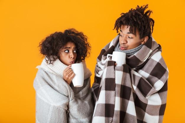Bevroren afrikaans paar dat in comfortabele dekens wordt verpakt die hete geïsoleerde thee drinken