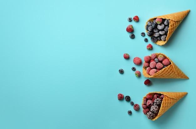 Bevroren bessen - aardbei, bosbes, braambes, framboos in wafelkegels op blauwe achtergrond.
