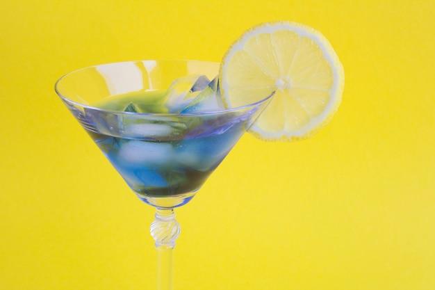 Bevroren blauwe drank met citroen in een martiniglas het geel
