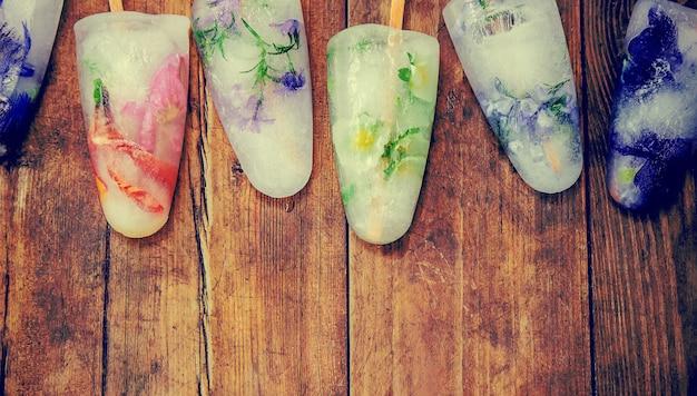 Bevroren bloemen in ijsblokjes en ijs op een stok. selectieve aandacht.