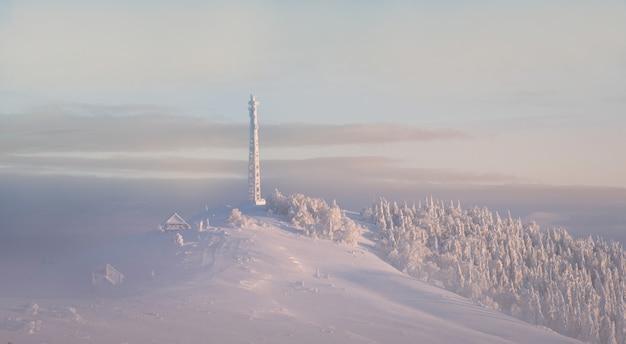 Bevroren cellulaire toren. bevroren telecommunicatietorens met schotel en mobiele antenne tegen blauwe hemel in de winterbergen.