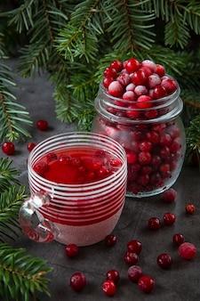 Bevroren cranberry bessen in een pot en cranberry sap in een glas op tafel versierd met takken van de kerstboom.