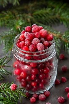 Bevroren cranberry bessen in een pot op tafel versierd met takken van de kerstboom.