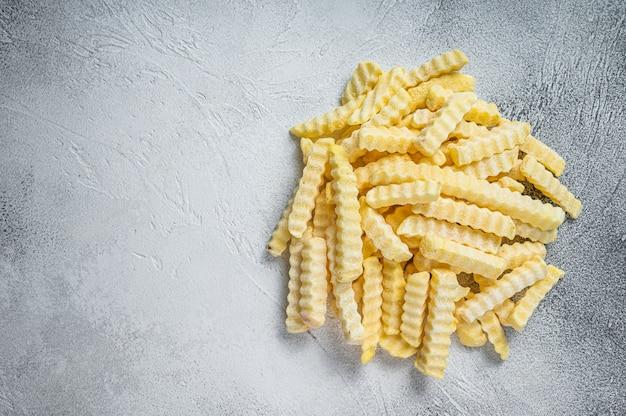 Bevroren crinkle frieten aardappelsticks. witte achtergrond. bovenaanzicht. ruimte kopiëren.