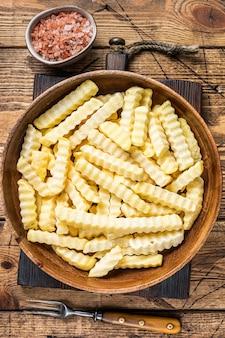 Bevroren crinkle oven frieten aardappelen stokken in een houten plaat. houten achtergrond. bovenaanzicht.