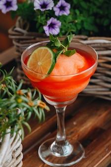 Bevroren de cocktailclose-up van aardbeimargarita naast bloemen