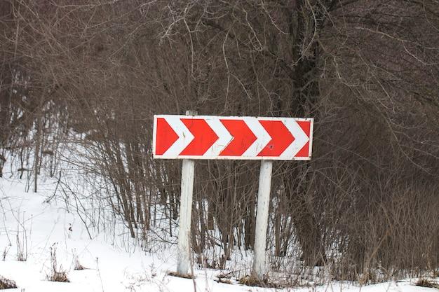Bevroren en besneeuwde gids verkeersbord van bocht en boom