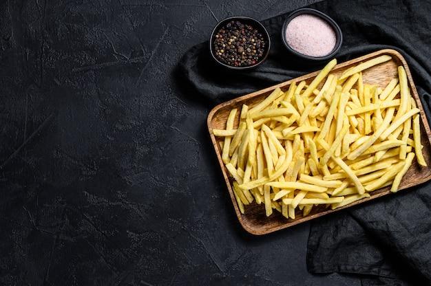 Bevroren frieten in een houten kom. biologische aardappelen. bovenaanzicht
