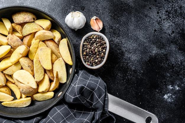 Bevroren frietjes aardappelpartjes. zwarte achtergrond. bovenaanzicht. kopieer ruimte