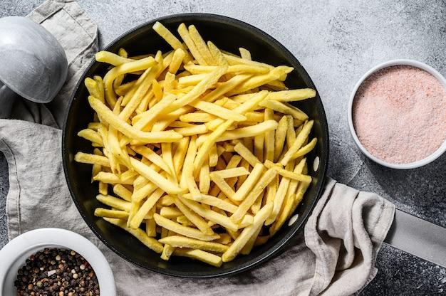 Bevroren frietjes in een koekenpan. grijze achtergrond. bovenaanzicht