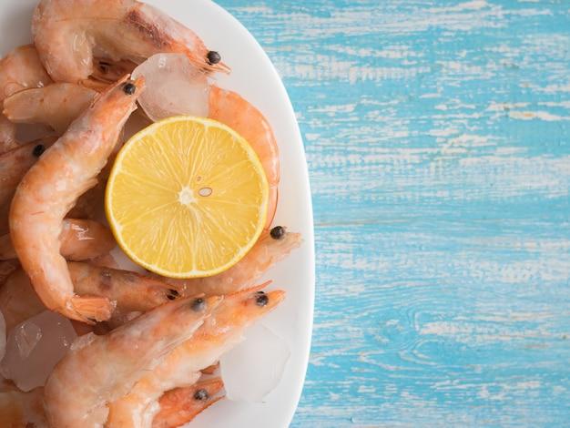 Bevroren garnalen in een aardewerk witte kom met citroen op een houten tafel