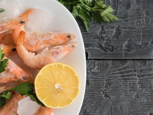 Bevroren garnalen met citroen en kruiden op witte kom op zwarte houten rustieke tafel bovenaanzicht