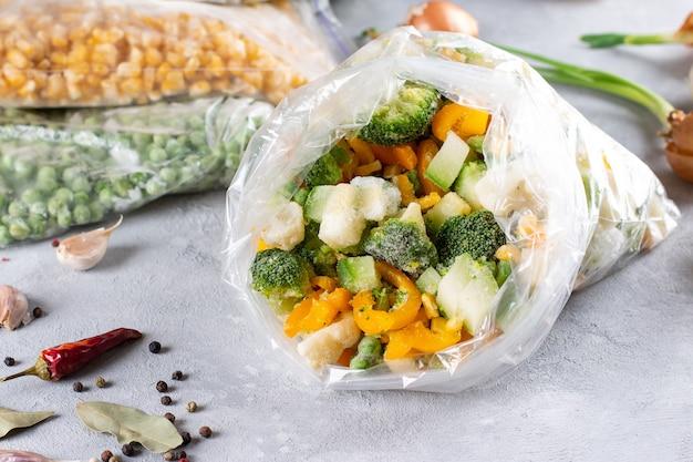 Bevroren gemengde groenten in een zak op een lichte betonnen achtergrond. diepvries voedsel. voedselopslag