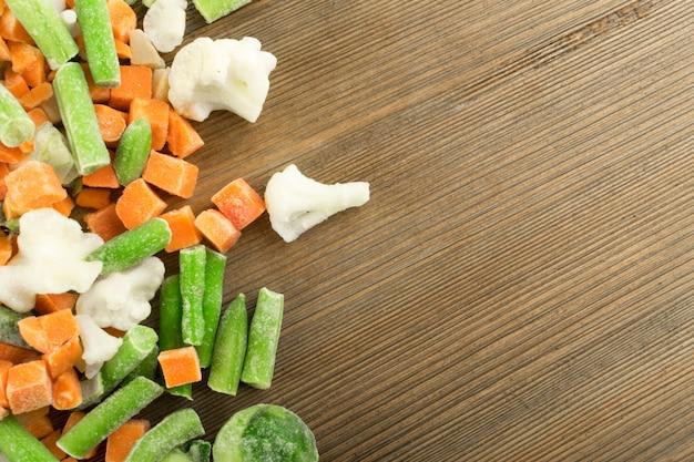 Bevroren gemengde groenten op houten achtergrond. rauwe gehakte wortel, bloemkool, ui, sperziebonen en spruitjes