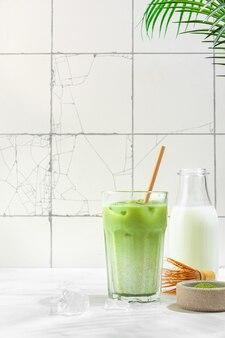 Bevroren groene matcha latte in een glas op een wit tegeloppervlak met harde schaduwen en palmbladeren