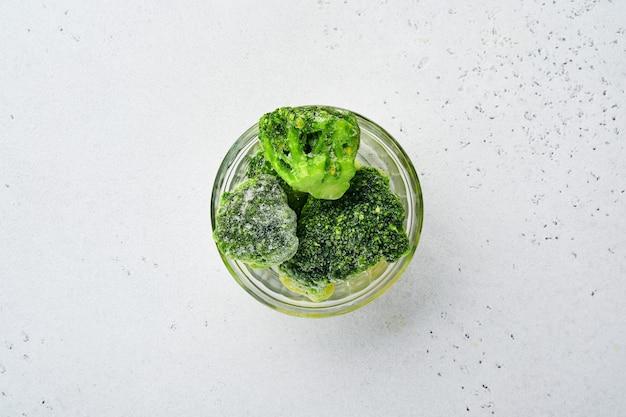Bevroren groenten groene broccoli in glazen kommen op ijs en betonnen grijze tafel met kopie ruimte.