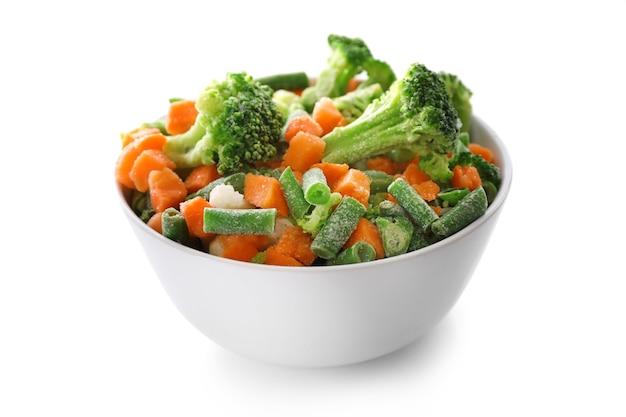 Bevroren groenten in kom die op wit wordt geïsoleerd