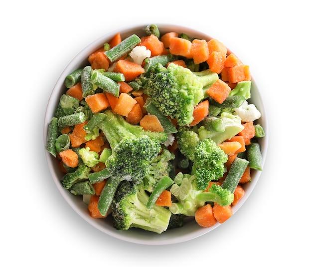 Bevroren groenten in kom geïsoleerd op wit bovenaanzicht