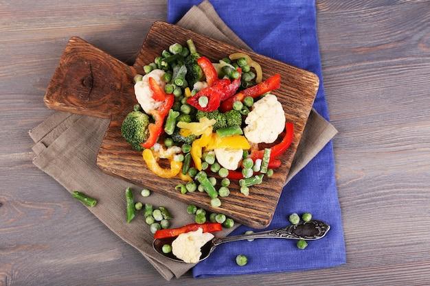 Bevroren groenten op snijplank, op servet, op houten tafel