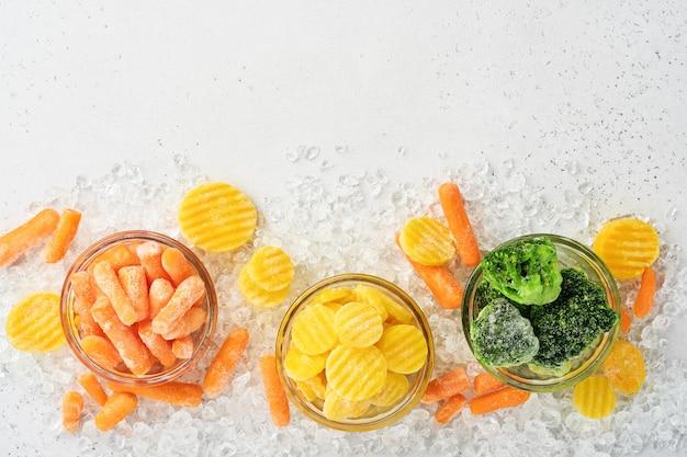 Bevroren groenten zoals groene broccoli, gele en babywortel in glazen kommen op ijs en betonnen grijze tafel met kopie ruimte.