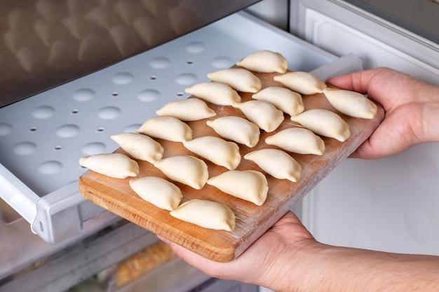 Bevroren halffabrikaten knoedels in de vriezer. levering van eten en eten thuis concept. bevroren voedsel concept.