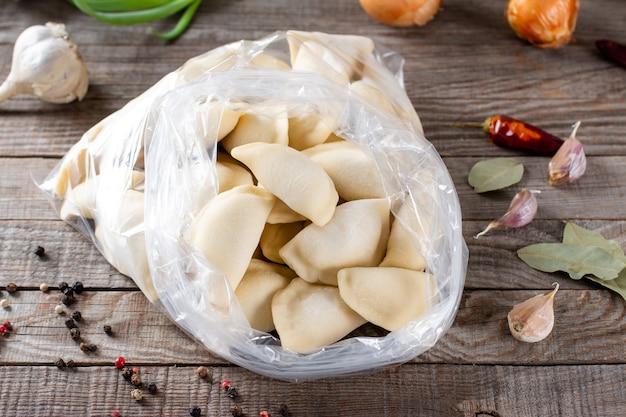 Bevroren halffabrikaten op een houten tafel met ingrediënten. russische knoedels. vleesballetjes, ravioli. dumplings met vulling
