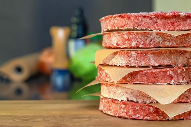 Bevroren hamburgerpasteitjes, ontdooien voor het grillen, gestapeld op het aanrecht.