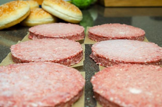 Bevroren hamburgervlees op tafel voor het grillen, ontdooien voor het grillen.