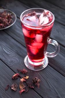 Bevroren hibiscus of karkadethee in het glas op de zwarte houten