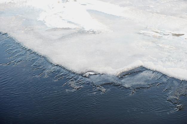 Bevroren ijs op de rivier - sneeuw en ijsheuveltjes