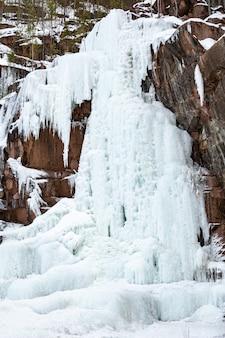 Bevroren ijs op de rotsen van een waterval in de bergen