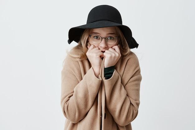 Bevroren jonge vrouw die in laag verpakken die gezicht behandelen met handen die ogen vol spanning hebben. zware mooie vrouw retro jas dragen en hoed die paniek hebben die proberen zich te concentreren en oplossing te vinden.