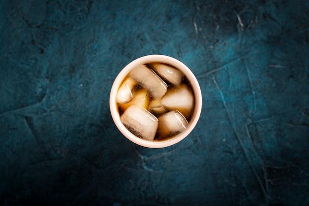 Bevroren koffie in een glas op een donkerblauwe stenen ondergrond. concept koeling drankje, dorst, zomer. plat lag, bovenaanzicht