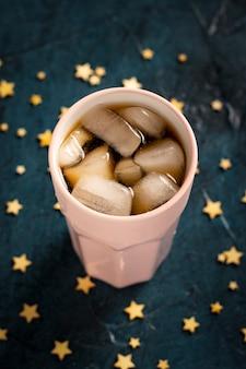 Bevroren koffie in een glas op een donkerblauwe stenen oppervlak met sterren. plat lag, bovenaanzicht