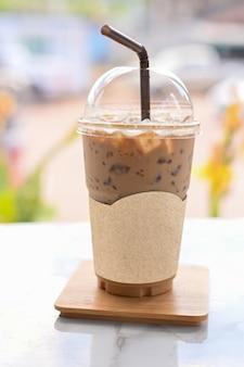Bevroren koffie in take away kopje plastic glas op de houten tafel in café met uitknippad op blanco label papier voor mockup cafe logo
