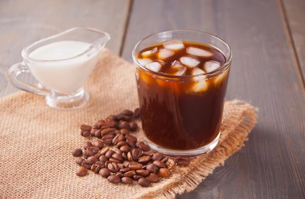 Bevroren latte koffie met ijsblokjes en koffiebonen op een tafel.