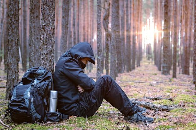 Bevroren moe reiziger man bij stilstand. toeristische rust in het bos.