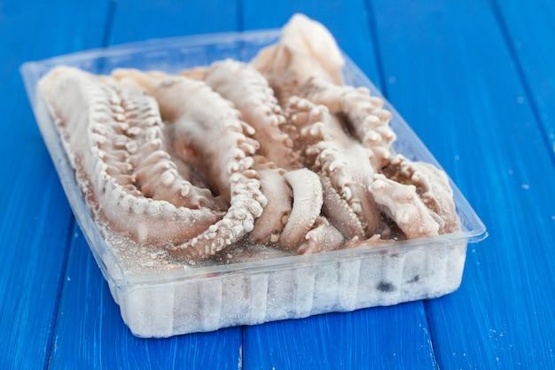 Bevroren octopus in de plastic doos op houten oppervlak