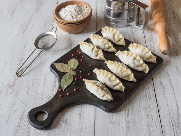 Bevroren ongekookte bollen op een houten raad. traditioneel zelfgemaakt eten. bovenaanzicht
