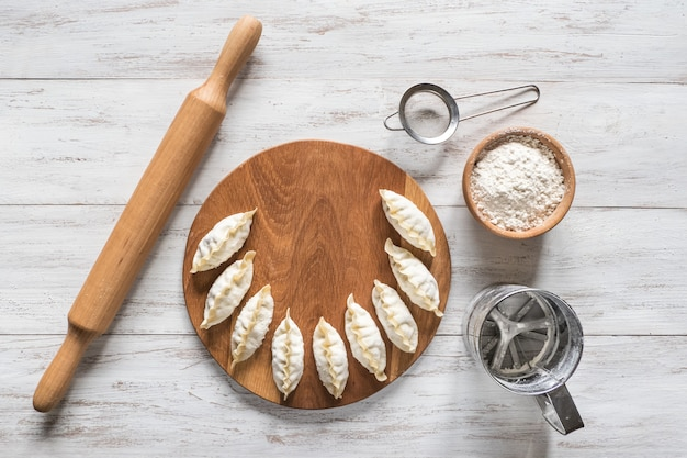 Bevroren ongekookte knoedels op een licht bord. traditioneel zelfgemaakt eten. bovenaanzicht