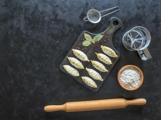 Bevroren ongekookte knoedels op een zwarte raad. traditioneel zelfgemaakt eten. bovenaanzicht