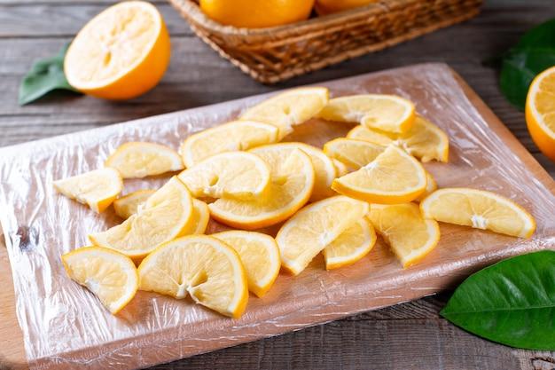 Bevroren plakjes citroen op een snijplank op een houten tafel