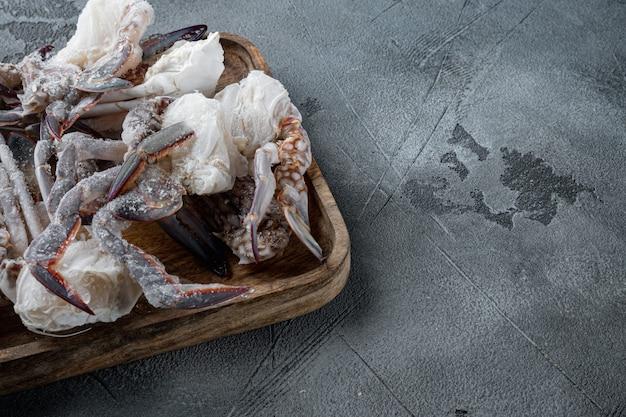 Bevroren rauwe blauwe zwemmende krabvleesreeks, op houten dienblad, op grijze achtergrond, met copyspace en ruimte voor tekst