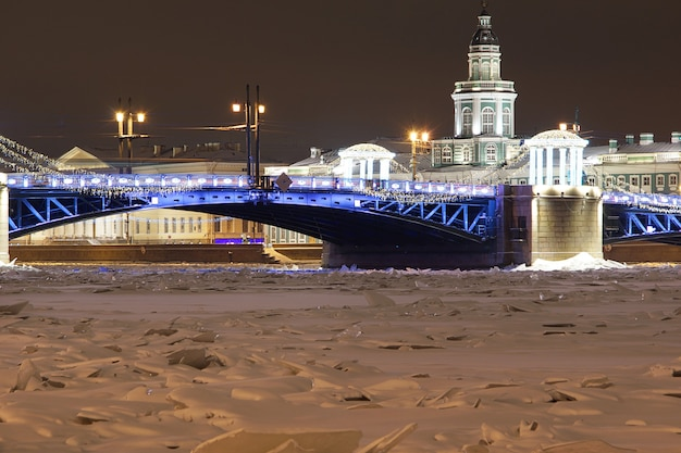 Bevroren rivier, mooie gloeiende brug met kerstversiering.
