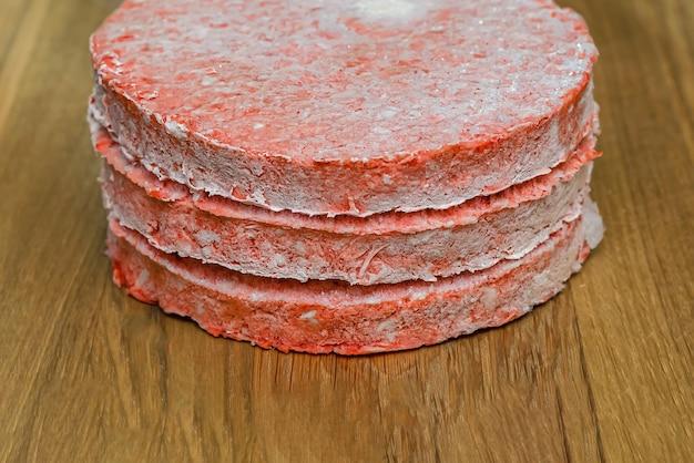 Bevroren rundvleesburgerpasteitjes worden voor het koken op een houten snijplank geplaatst. invriezen in de vriezer.